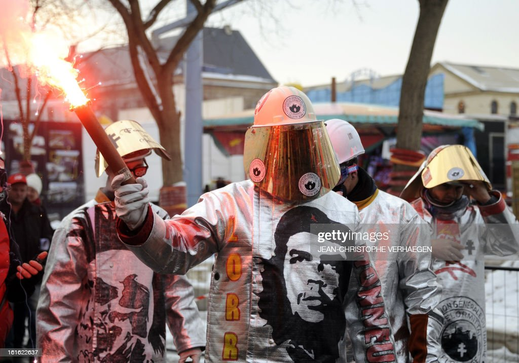 A steel industry worker (C) holds a flare, wearing a full-body suit bearing a picture of Argentine-born Cuban revolution hero Che Guevara, during a demonstration called by French CGT trade union on February 13, 2013 in Metz, eastern France, to claim for the safeguard of the local industry in the French eastern region of Lorraine.