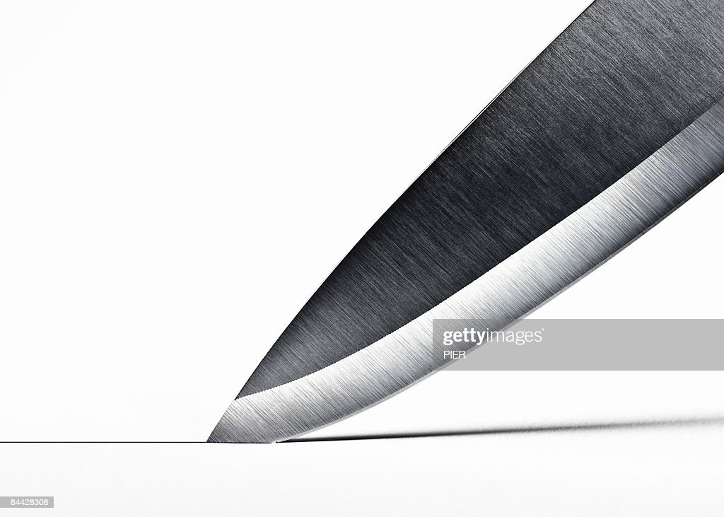 Steel knife blade cutting into surface