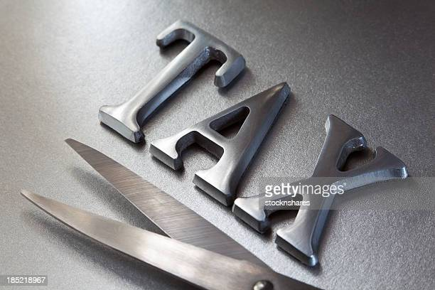Steel letters and scissors representing tax cuts