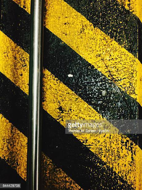 Steel Pole Against Yellow And Black Striped Wall