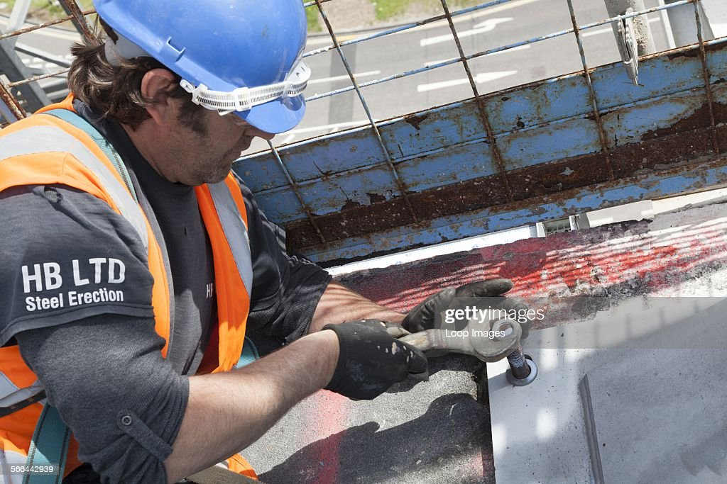 Steel rigger tightening nut on steelwork on a construction site