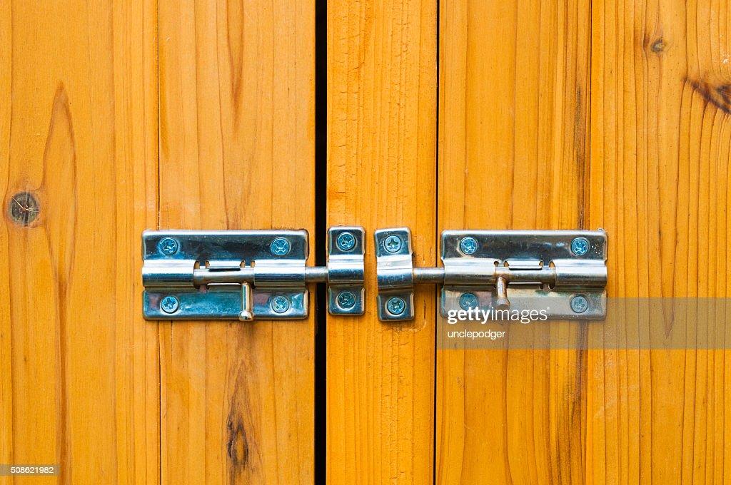 Steel slide locks on wooden door : Stock Photo
