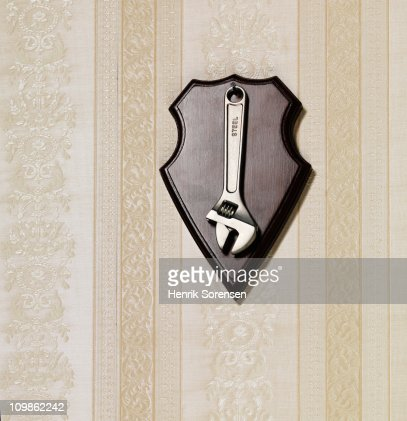Steel spanner hanging as a trophy on a wall : Stock Photo