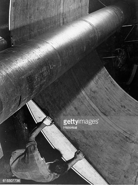 Steel under giant rolls being shaped for submarine construction at Electric Boat Company Groton Connecticut August 1943 | Location Electric Boat...