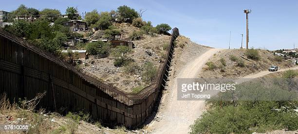 A steel wall separates Nogales Sonora Mexico from a US Border Patrol agent in his sector May 14 2006 in Nogales Arizona US President George W Bush...