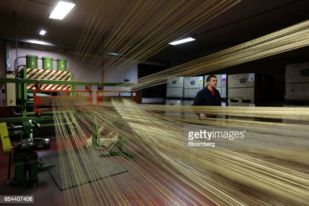 Steel wire cord passes through a machine during the calendering process to fabricate rubber tires at the Belshina JSC tire factory in Babruysk...