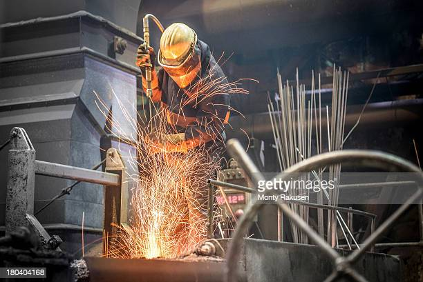 Steel worker amid sparks from molten steel in industrial foundry