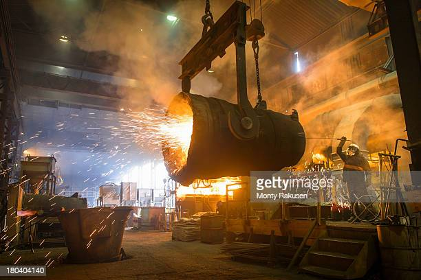 Steel worker cleaning large ladle in an industrial foundry