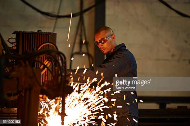 Steel worker cutting out steel at factory