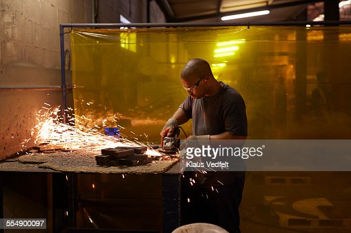 Steel worker cutting steel items at factory : Stock Photo