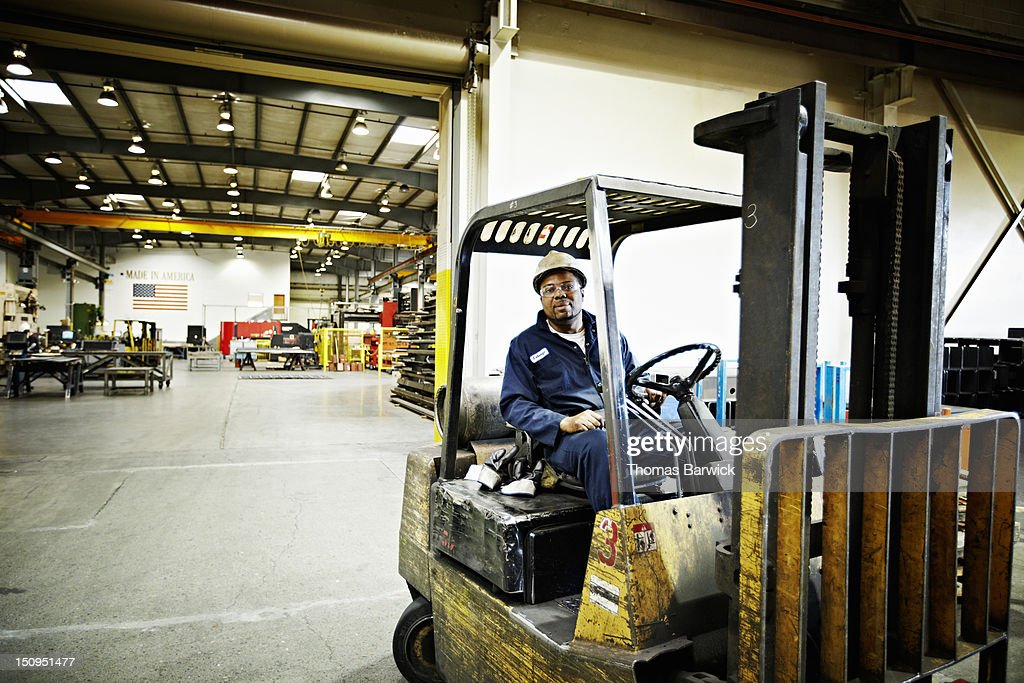 Steel worker driving forklift