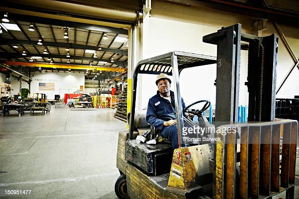 Steel worker driving forklift