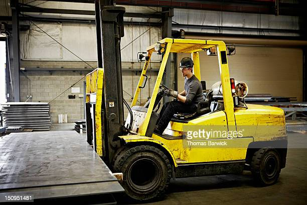 Steel worker driving forklift to move steel