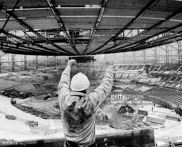 Steel worker giving the hold signal as the Madison Square Garden roof support tower is lowered by four 160ton hydraulic jacks marking the completion...