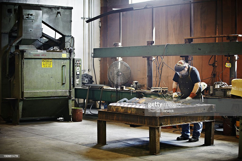 Steel worker grinding metal pieces
