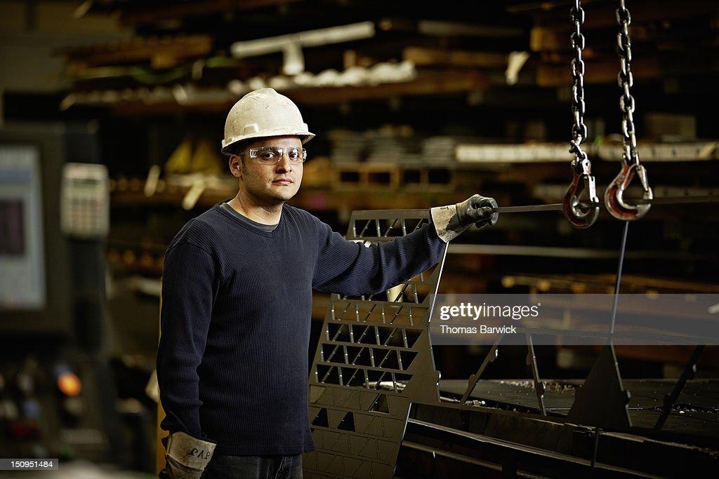 Steel worker holding sheet of laser cut steel