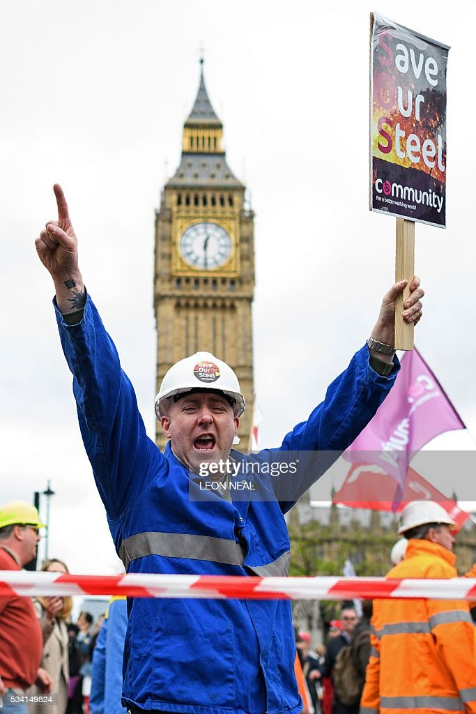 A steel worker holds a placard as he passes The Houses of Parliament during a protest march through central London on May 25, 2016. Britain's business minister Sajid Javid met Tata Steel bosses in Mumbai ahead of a crunch board meeting on Wednesday expected to discuss potential buyers for its loss-making UK assets. Tata Steel, Britain's biggest steel employer, announced in March that it planned to sell its Port Talbot plant in Wales and other assets, putting 15,000 jobs at risk. / AFP / LEON