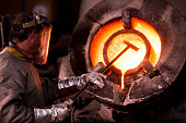 Steel worker in protective clothing raking furnace in an industrial foundry