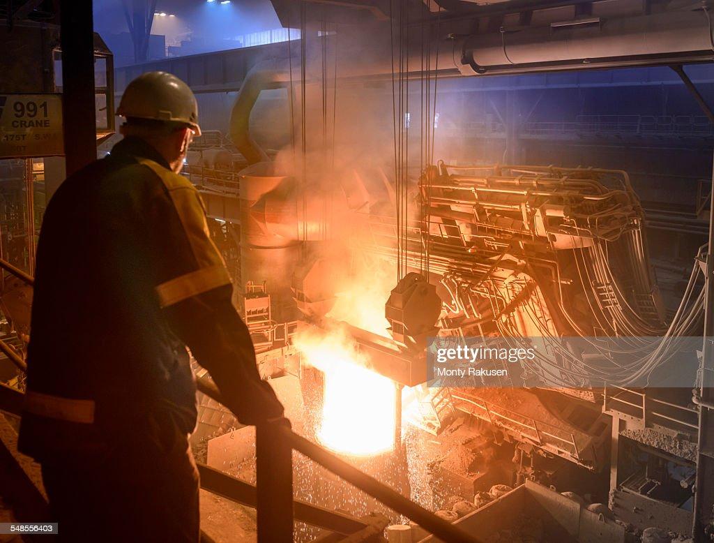 Steel worker inspecting pouring molten steel