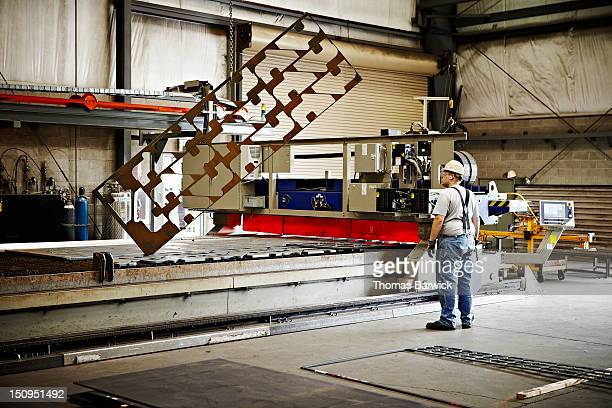 Steel worker lifting sheet of metal with crane