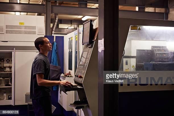 Steel worker operating big laser cutter