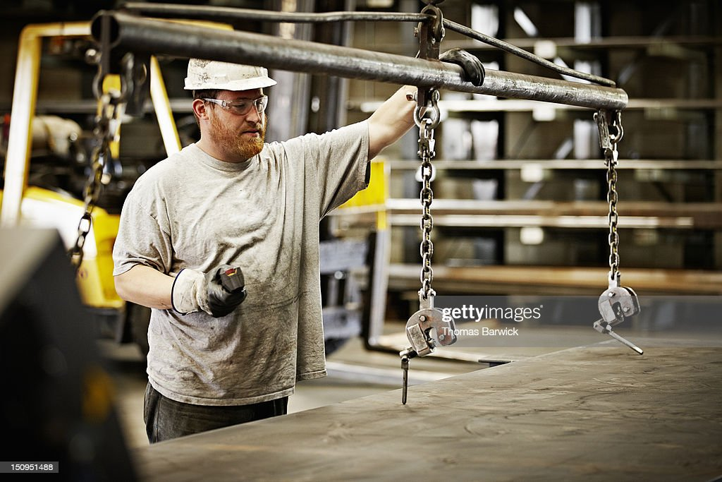 Steel worker preparing to move steel with crane : Stock Photo