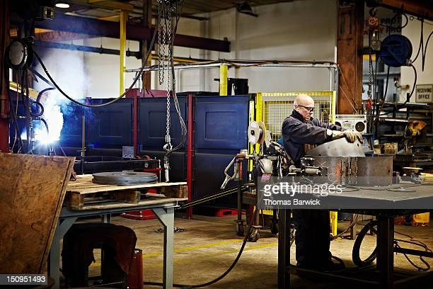 Steel worker preparing to weld cylinder