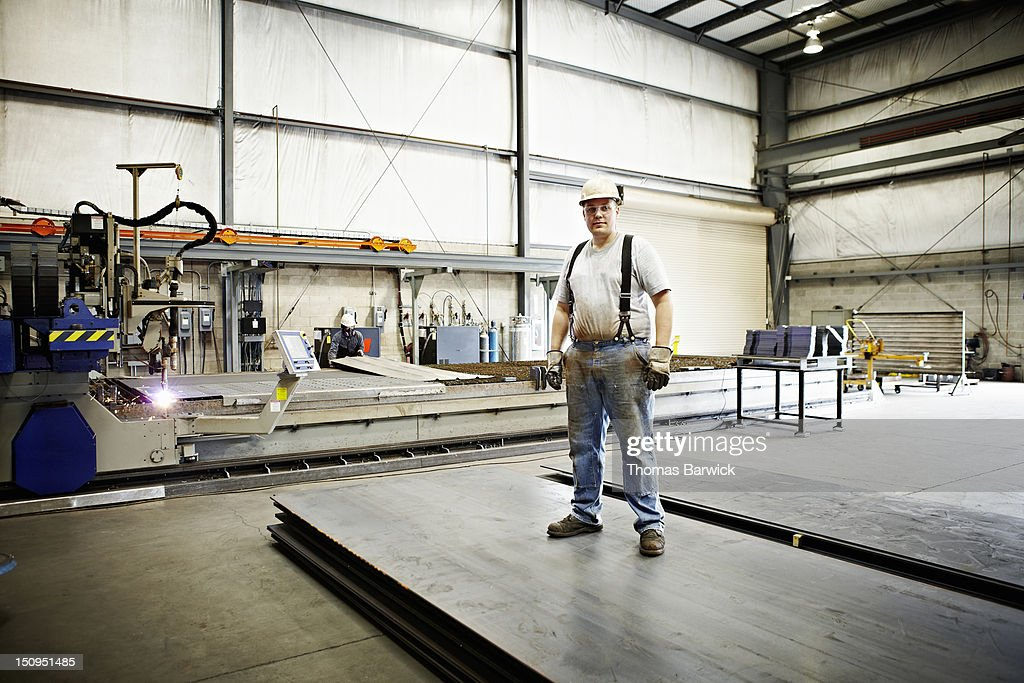 Steel worker standing on sheets of steel smiling : Stock Photo