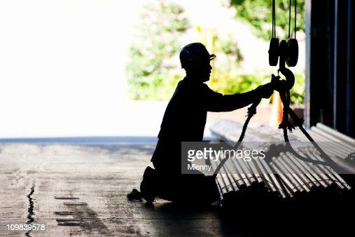 Steel worker tying metal tubes to crane jib in warehouse