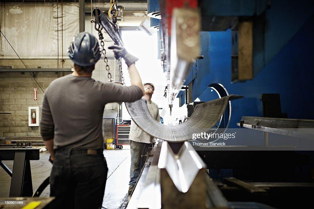 Steel workers adjusting position of steel : Stock Photo