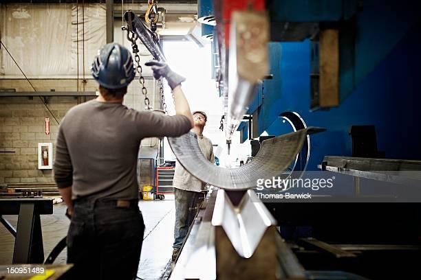 Steel workers adjusting position of steel