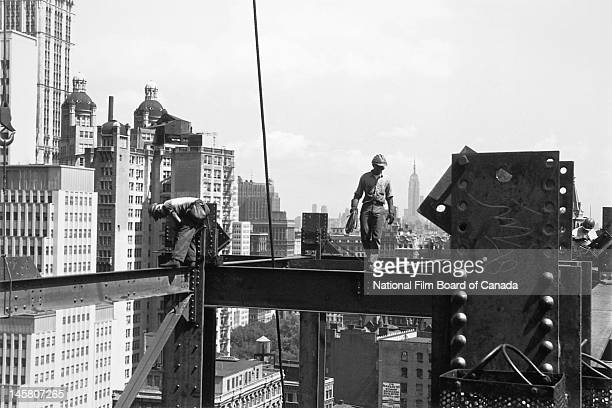 Steel workers are at work high above street level on the construction of a skyscraper New York New York 1964 Photo taken during the National Film...
