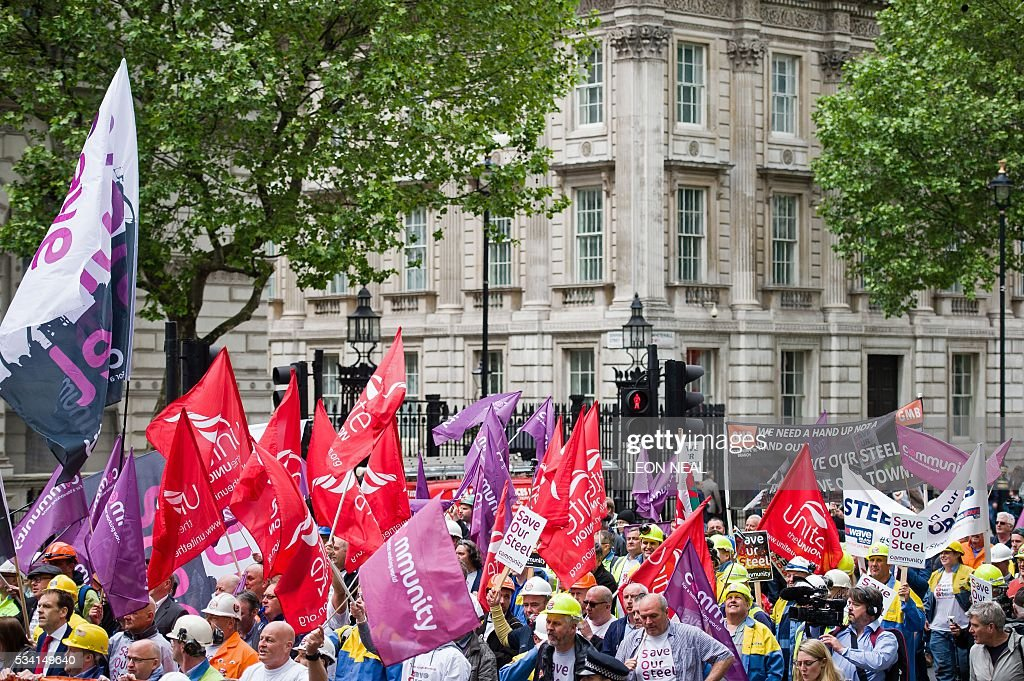Steel workers hold placards and wave banners as they pass Downing Street during a protest march through central London on May 25, 2016. Britain's business minister Sajid Javid met Tata Steel bosses in Mumbai ahead of a crunch board meeting on Wednesday expected to discuss potential buyers for its loss-making UK assets. Tata Steel, Britain's biggest steel employer, announced in March that it planned to sell its Port Talbot plant in Wales and other assets, putting 15,000 jobs at risk. / AFP / LEON
