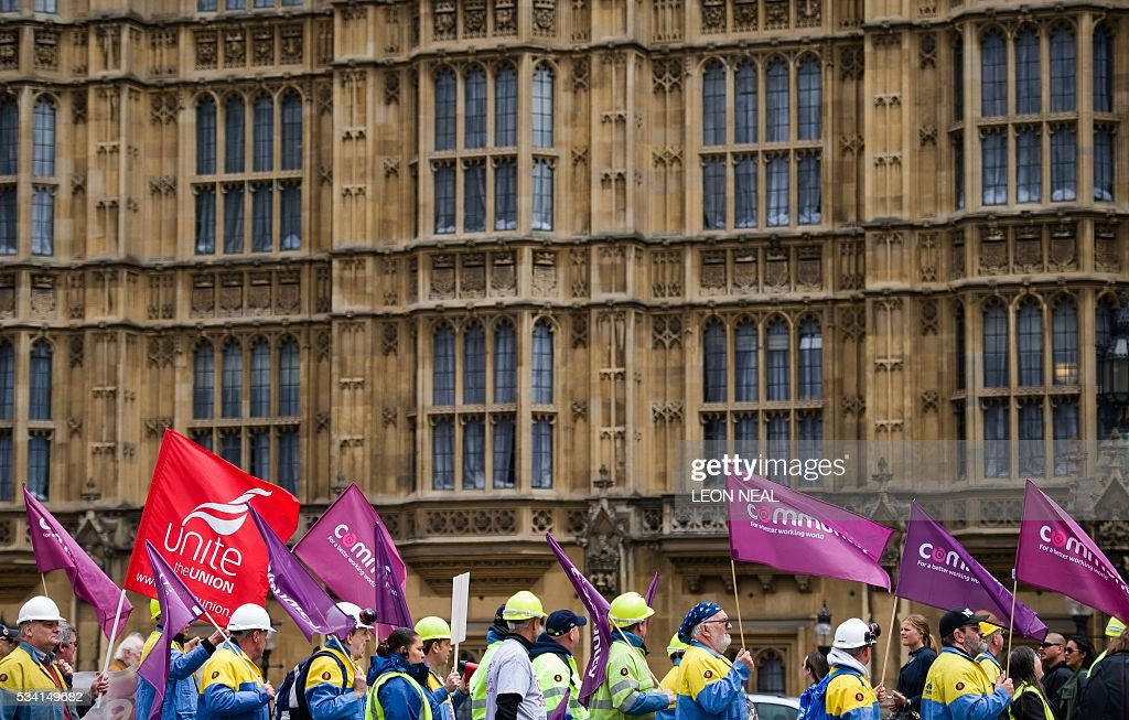 Steel workers hold placards and wave banners as they pass The Houses of Parliament during a protest march through central London on May 25, 2016. Britain's business minister Sajid Javid met Tata Steel bosses in Mumbai ahead of a crunch board meeting on Wednesday expected to discuss potential buyers for its loss-making UK assets. Tata Steel, Britain's biggest steel employer, announced in March that it planned to sell its Port Talbot plant in Wales and other assets, putting 15,000 jobs at risk. / AFP / LEON