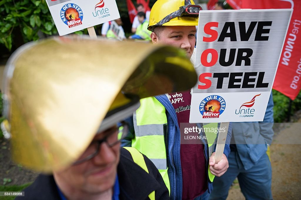 Steel workers hold placards as they take part in a protest march through central London on May 25, 2016. Britain's business minister Sajid Javid met Tata Steel bosses in Mumbai ahead of a crunch board meeting on Wednesday expected to discuss potential buyers for its loss-making UK assets. Tata Steel, Britain's biggest steel employer, announced in March that it planned to sell its Port Talbot plant in Wales and other assets, putting 15,000 jobs at risk. / AFP / LEON