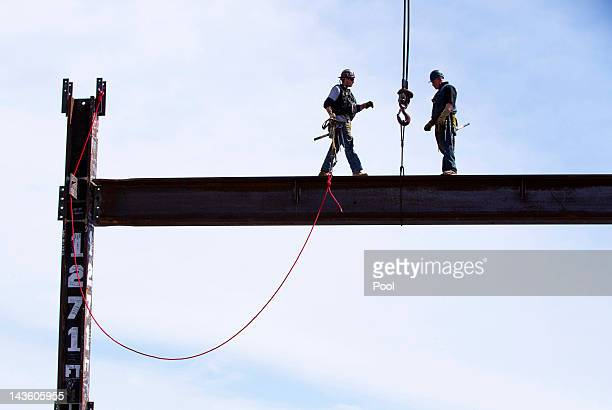 Steel workers Jim Brady and Billy Geoghan walk onto a steel beam after maneuvering it into place on the 100th story at the top of One World Trade...
