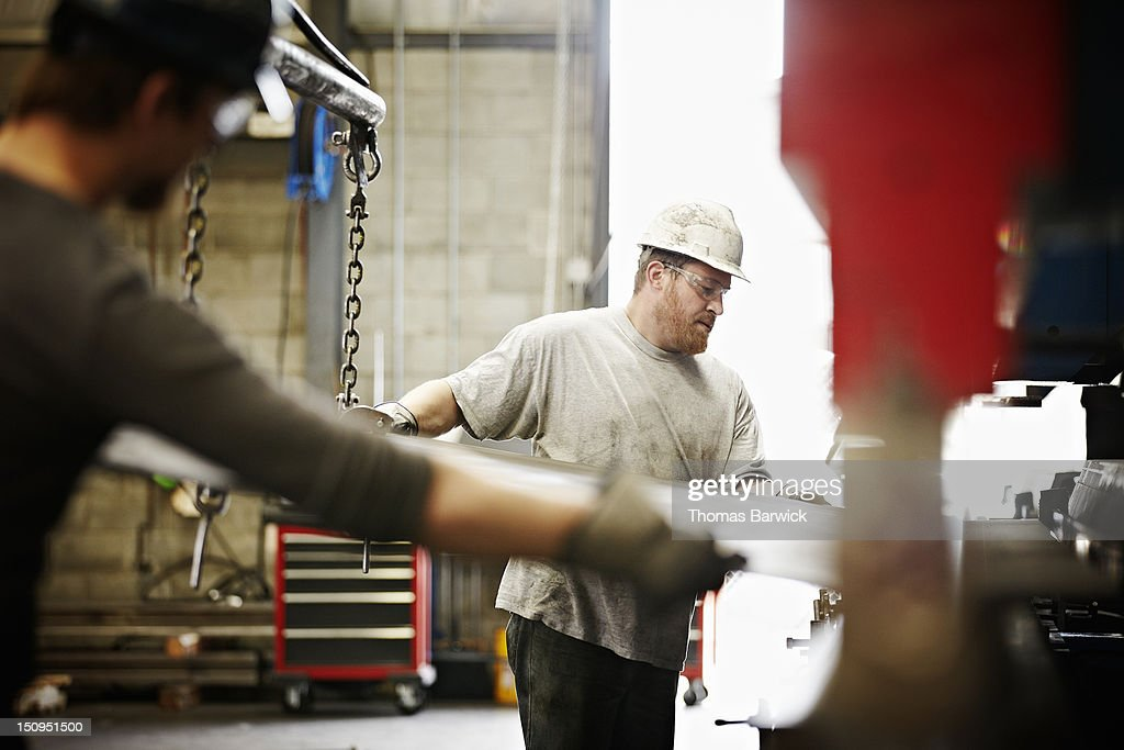 Steel workers placing steel in brake press