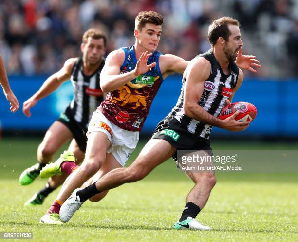 Steele Sidebottom of the Magpies is tackled by Ben Keays of the Lions during the 2017 AFL round 10 match between the Collingwood Magpies and the...