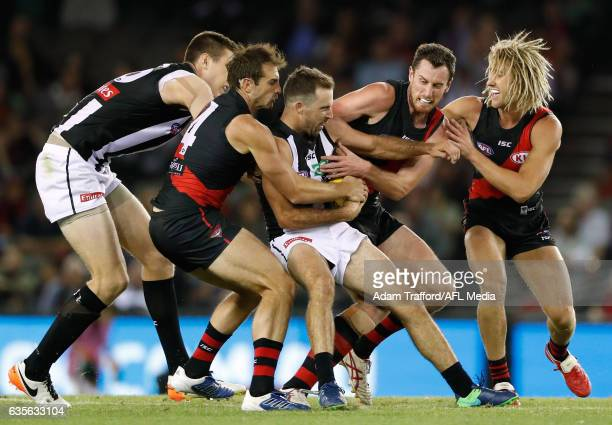 Steele Sidebottom of the Magpies is tackled by Jobe Watson Matthew Leuenberger and Dyson Heppell of the Bombers during the AFL 2017 JLT Community...