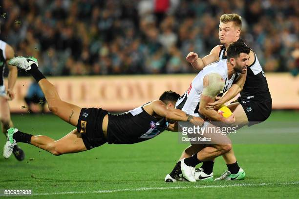 Steele Sidebottom of the Magpies is tackled by Ollie Wines and Jarman Impey of the Power during the round 21 AFL match between Port Adelaide Power...