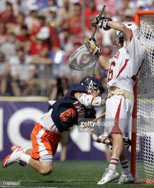 Steele Stanwick of the Virginia Cavaliers gets the ball past goalie Jamie Faus of the Denver Pioneers for a goal during the first half at MT Bank...