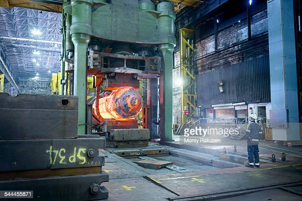 Steelworker inspects hot steel in forging press in steelworks