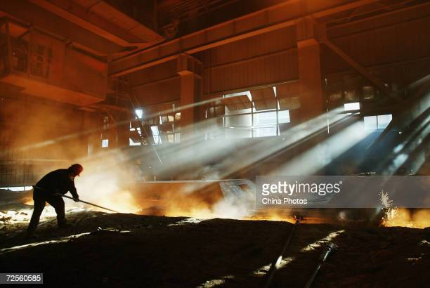 A steelworker works at a steel mill of the Baotou Iron and Steel Group on November 26 2004 in Baotou China The group is one of the largest production...
