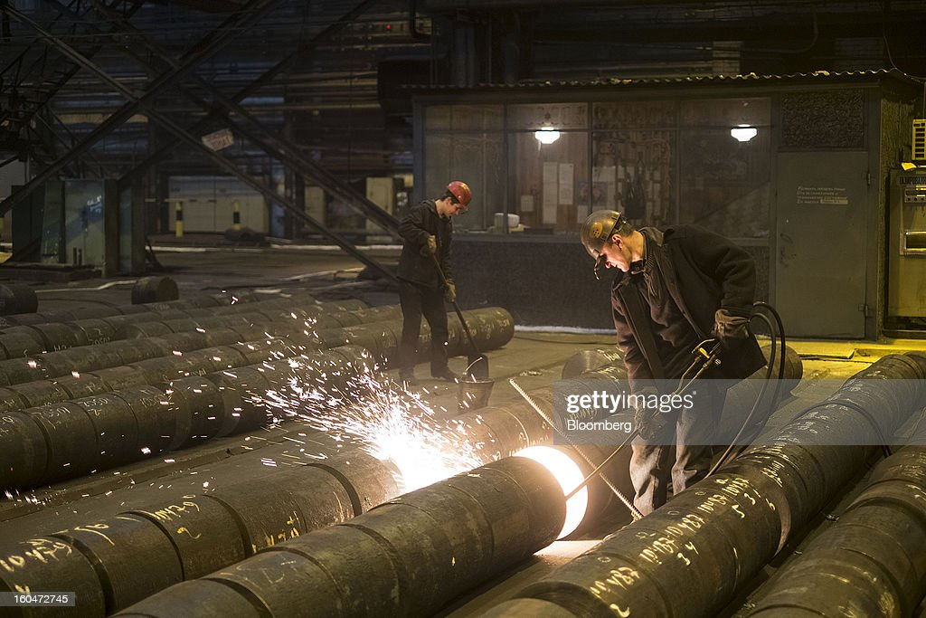 Steelworkers grind the ends of steel billets before pressing at the Interpipe LLC plant in Dnipropetrovsk, Ukraine, on Wednesday, Jan. 30, 2013. Ukraine's Interpipe Group, owned by billionaire Victor Pinchuk, opened a $700 million electric steel mill in Dnipropetrovsk with an annual output capacity of 1.32 million tons of steel for its seamless pipe production. Photographer: Vincent Mundy/Bloomberg via Getty Images