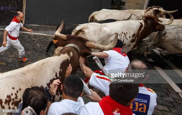 CORRECTION A steer hits a participant's head with its horn on the first day of the San Fermin bull run festival in Pamplona northern Spain on July 7...