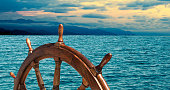 Steering wheel at sea background.  Skipper's wheel on an old ship. Sea voyage at the seaside with captains wheel of the old vessel, closeup.