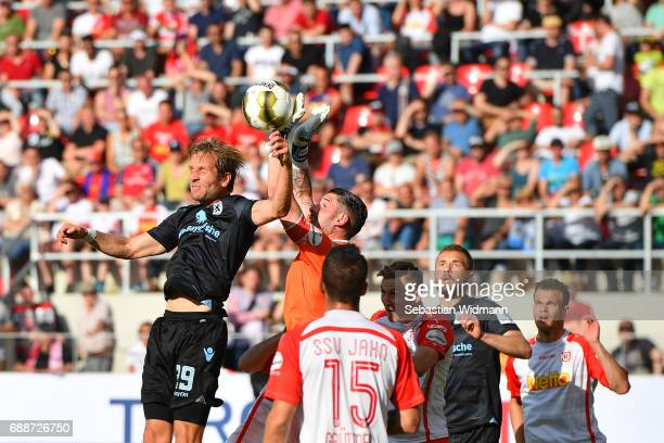 Stefan Aigner of 1860 Muenchen jumps for a header with goalkeeper Philipp Pentke of Jahn Regensburg during the Second Bundesliga Playoff first leg...