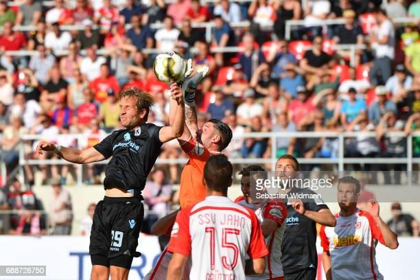 Stefan Aigner of 1860 Muenchen jumps for a header with goalkeeper Philipp Pentke of Jahn Regensburg during the Second Bundesliga Playoff first leg...