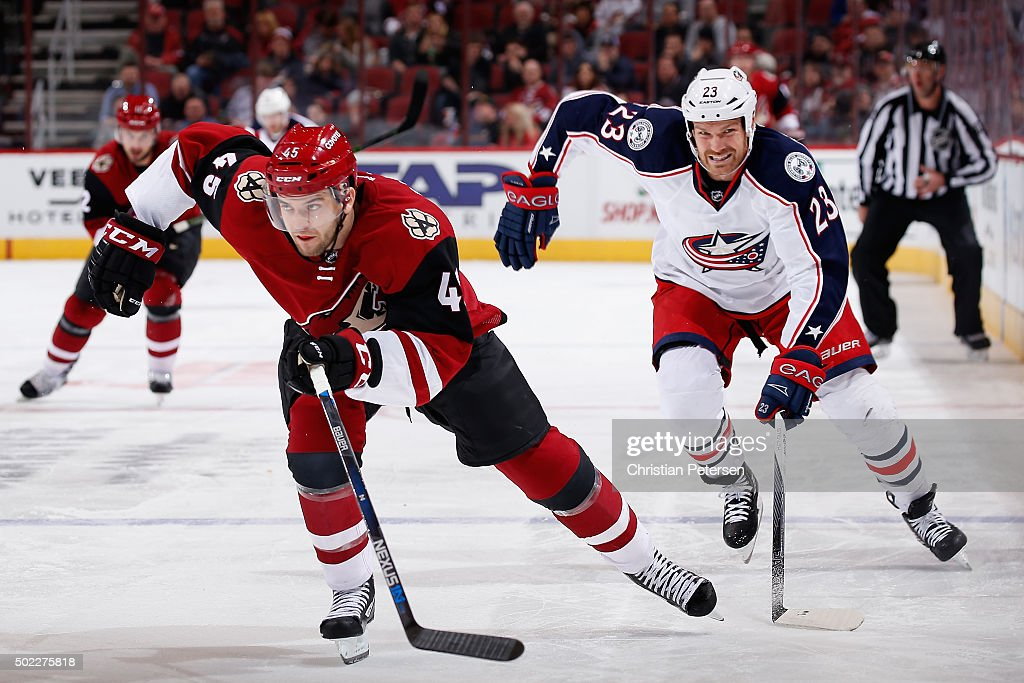 Stefan Elliott of the Arizona Coyotes skates ahead of David Clarkson of the Columbus Blue Jackets during the NHL game at Gila River Arena on December...