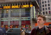 Stefan Fredrick of New York who says he has 'too much' money in Nasdaq stocks peers through the window of the Nasdaq building in Times Square in New...